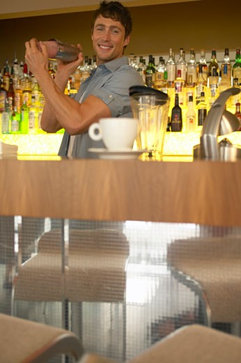 Stock Photo: 1598R-9956601 Man working behind bar, shaking cocktail mixer, smiling, portrait