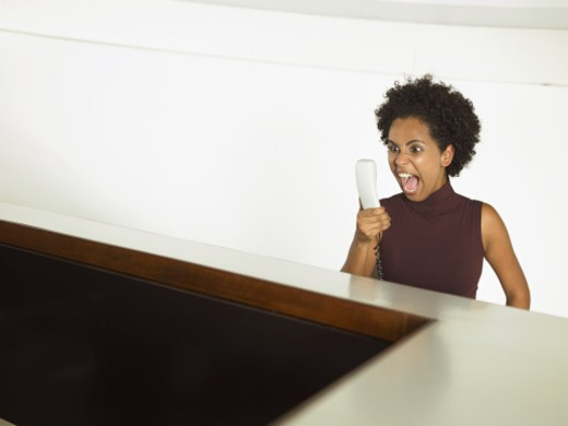 Woman screaming into phone receiver : Stock Photo