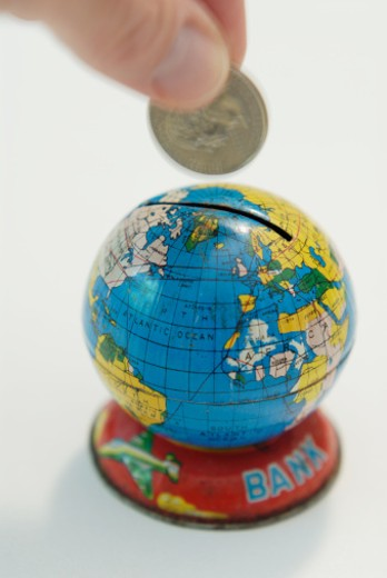 Man depositing pound coin into coin slot in globe, close-up : Stock Photo