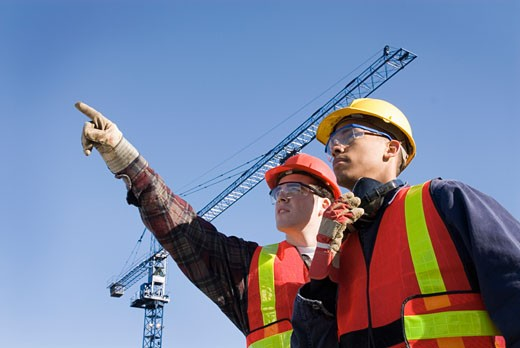 Two male construction workers on site, one pointing, crane in background : Stock Photo
