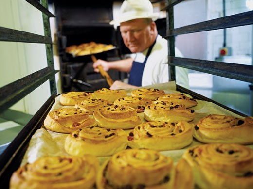 Baker Lifting a Tray of Danish Pastries From a Trolley, Food Processing, Grimsby, UK : Stock Photo