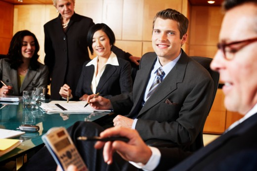 Businessman smiling at man using electronic organiser in meeting : Stock Photo