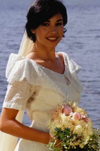 Stock Photo: 1598R-99576 Bride posing by lake, portrait