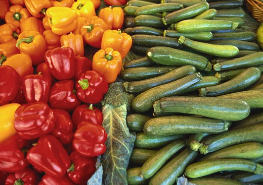 Red Peppers, Yellow Peppers and Courgettes on a Market Stall : Stock Photo
