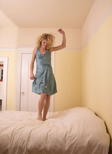 Young woman dancing on bed, smiling (blurred motion) : Stock Photo