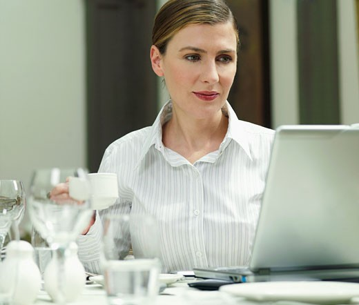Businesswoman using laptop in restaurant : Stock Photo