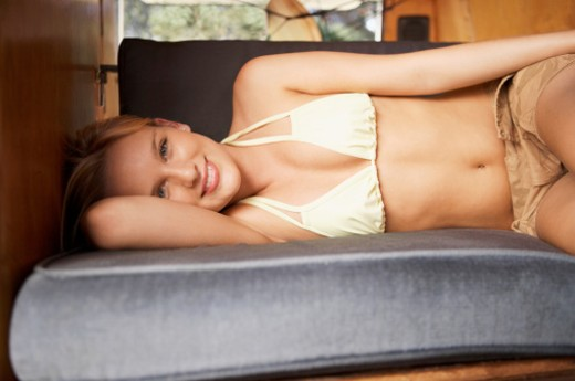 Portrait of a Young, Smiling Woman Lying on a Bench in a Caravan : Stock Photo