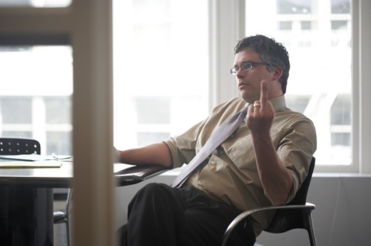 Business man sitting in office making rude gesture : Stock Photo