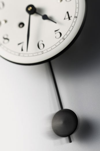 Stock Photo: 1598R-9958349 Pendulum Swinging From a Clock