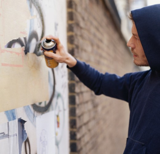 Stock Photo: 1598R-9958718 Young man wearing hooded top, spraying graffiti on wall, side view