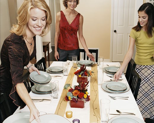 Stock Photo: 1598R-9958893 Well-Dressed Women and a Girl Set a Dining Table