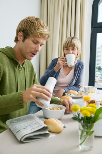 Couple eating breakfast at dining table : Stock Photo