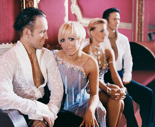 Stock Photo: 1598R-9959194 Four Well Dressed Ballroom Dancers Sitting on a Seat