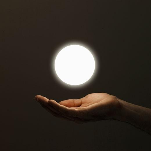 Stock Photo: 1598R-9959298 Hand below orb of light, close-up (digital enhancement)