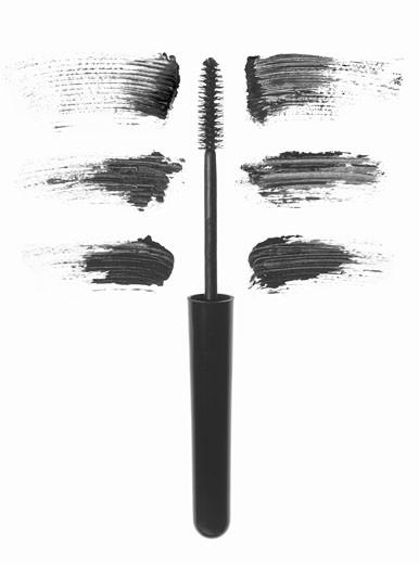 Mascara brush with smudges near it : Stock Photo