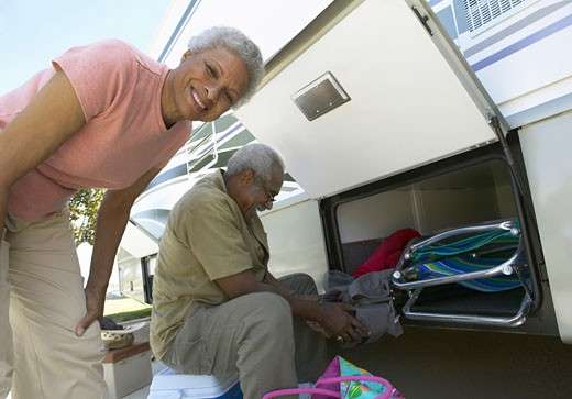 Senior Couple Unload Luggage From Their Motor Home : Stock Photo