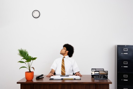 Man sitting at desk in office, looking over shoulder at clock : Stock Photo