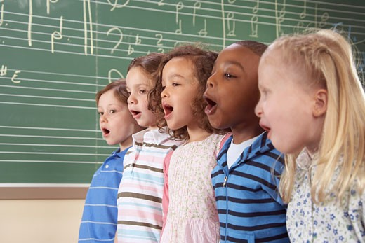 Five school children (5-10) singing in class, close-up : Stock Photo