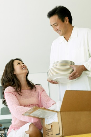 Couple Moving House Help Each Other Unload Plates From a Cardboard Box : Stock Photo