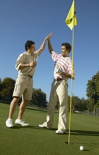 Stock Photo: 1598R-9960369 Two Brothers Stand on a Putting Green by a Golf Flag, Giving Each Other a High Five