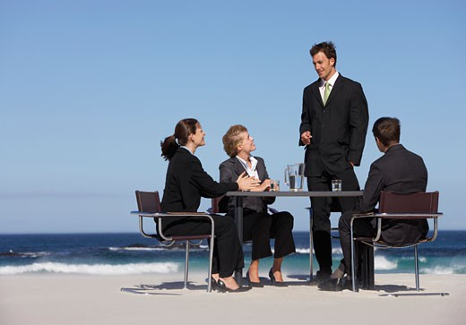 Stock Photo: 1598R-9960777 Four Well-Dressed Businessmen and Businesswomen Sit at a Table on a Beach, Having a Meeting