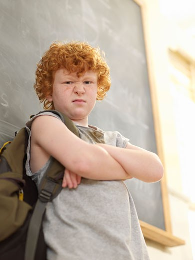 Angry boy (9-11) standing at blackboard in classroom portrait, low angle view : Stock Photo