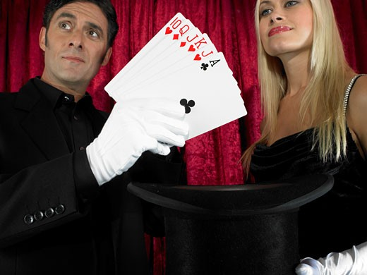 Magician performing card trick with female assistant : Stock Photo