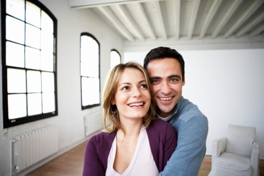 Stock Photo: 1598R-9961356 Couple embracing indoors, smiling, close-up