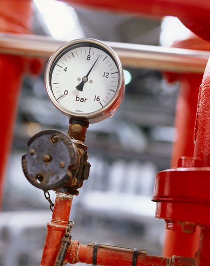 Close Up of a Pressure Gauge Attached to a Red Pipe in a Gas Fired Power Station : Stock Photo