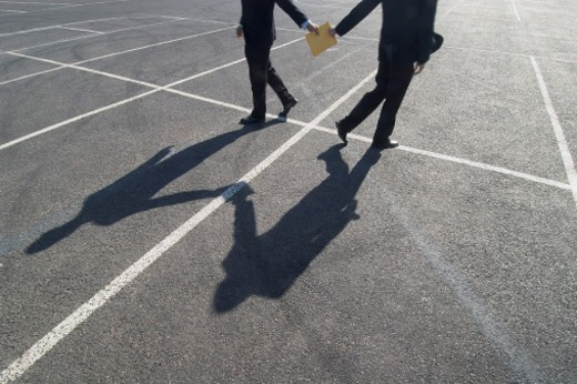 Criminal Businessman Passing a Folder to Another Businessman in a Carpark : Stock Photo