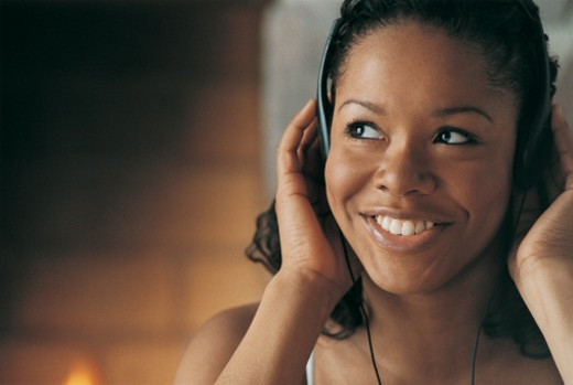 Portrait of a Young, Smiling Woman Listening to Music on Her Headphones : Stock Photo
