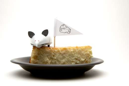 Stock Photo: 1598R-9962196 White wind-up mouse on cheesecake with cheese flag