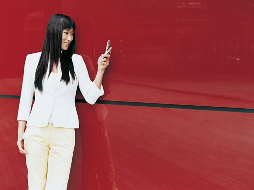 Businesswoman Leaning on a Red Building Exterior Dialling a Text on Her Mobile Phone : Stock Photo