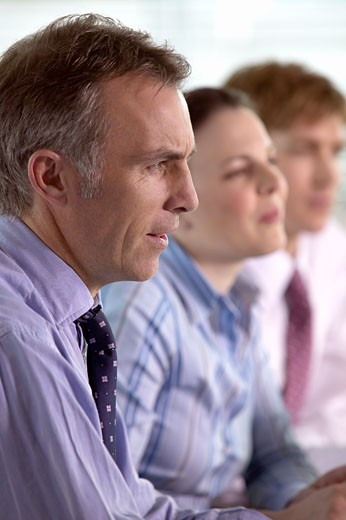Side View of Serious Businessman, and Colleagues in the Background : Stock Photo