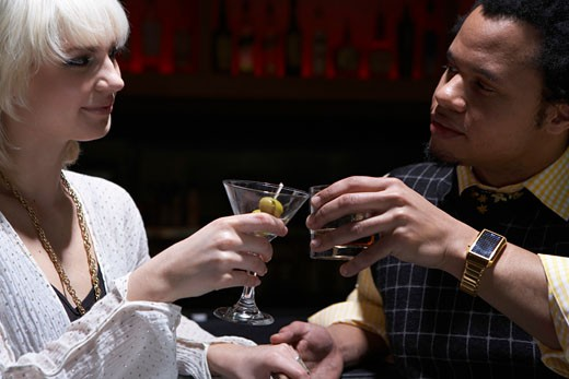 Young man and woman toasting with cocktails in nightclub : Stock Photo