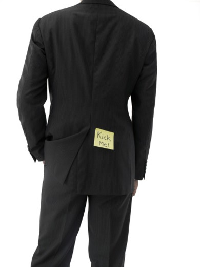 Businessman with 'kick-me' adhesive note on butt, mid section, rear view : Stock Photo