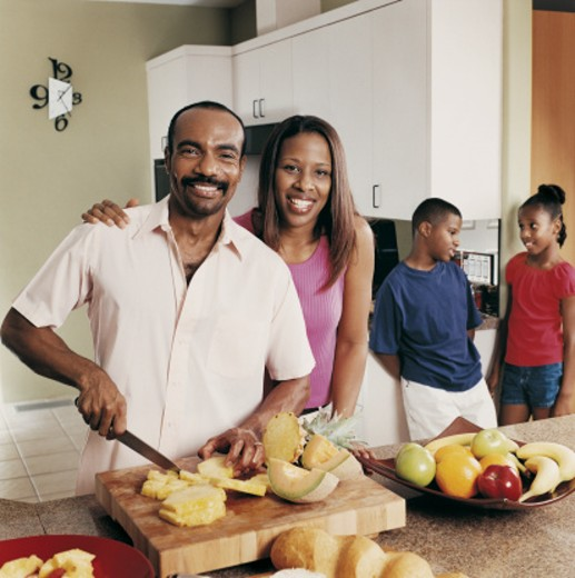 Family of Four in Kitchen Father Chopping Fruit : Stock Photo