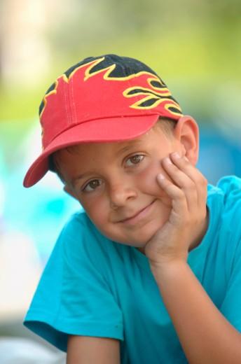 Stock Photo: 1598R-9963970 Boy (6-7) in baseball cap outdoors, resting head on hand, portrait