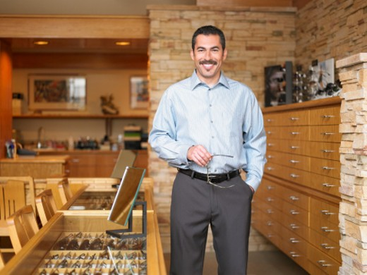 Stock Photo: 1598R-9964044 Male sales clerk standing in eyeglass store, portrait