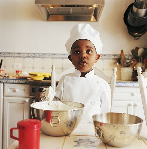 Boy (3-5) wearing chef outfit by bowls in kitchen : Stock Photo