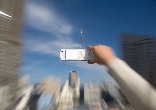Stock Photo: 1598R-9964096 Man holding mobile phone with cityscape in background