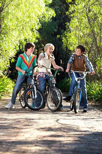 Three boys (9-13) on bikes, smiling : Stock Photo