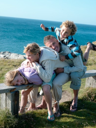Stock Photo: 1598R-9964433 Family with two children (7-10) hugging on bench at ocean