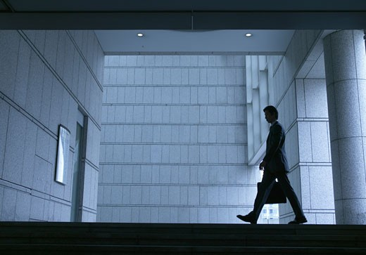 Businessman in Silhouette Walking Past a Stone Wall : Stock Photo