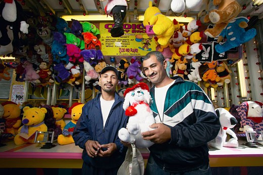 Men standing by soft toy stall, smiling, portrait : Stock Photo