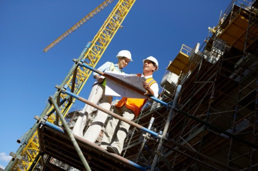 Stock Photo: 1598R-9965158 Two Well Dressed Colleagues Standing Side by Side on a Construction Frame, Looking at Blueprints