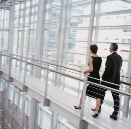 Rear View of Two Business Colleagues Walking Along an Elevated Walkway in a Modern Office : Stock Photo