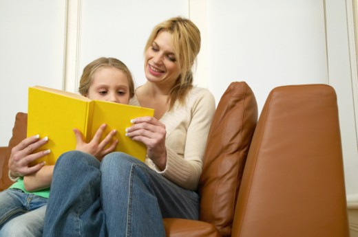 Mother and daughter (5-7) sitting on sofa reading book : Stock Photo