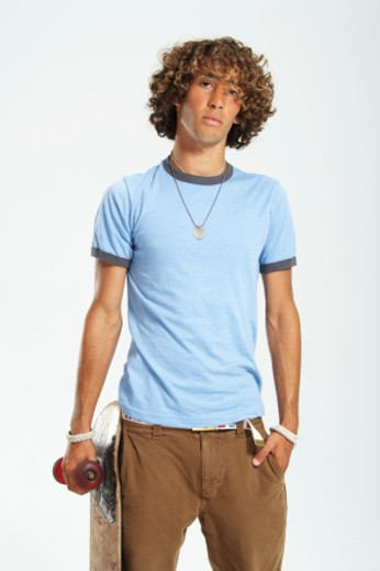Teenage boy (16-18) with curly hair, holding skateboard, portrait : Stock Photo