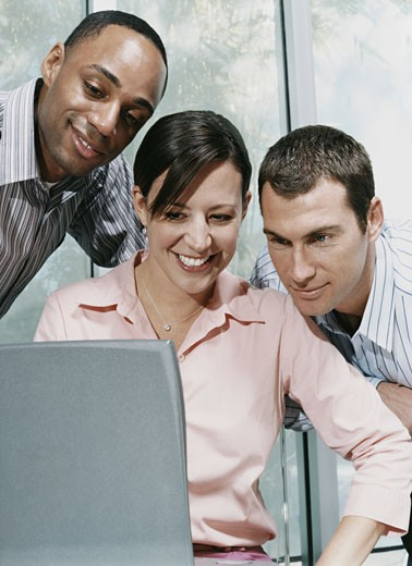 Three Business Colleagues Looking at a Laptop Computer : Stock Photo